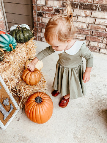 cute kid in green dress touching pumpkins on front porch