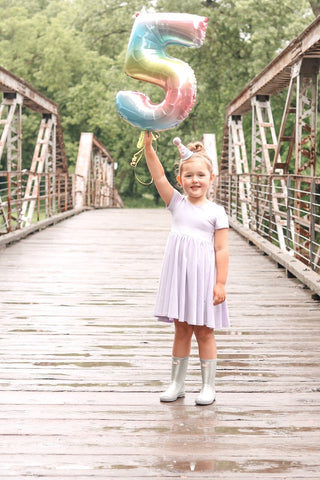 girl holding number 5 balloon and birthday hat standing on a bridge