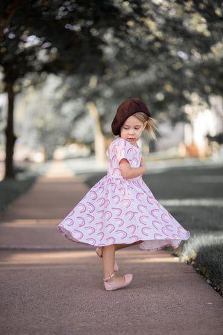 young girl in beret twirling in rainbow print dress