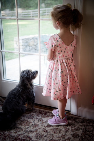girl and dog standing at door looking out window