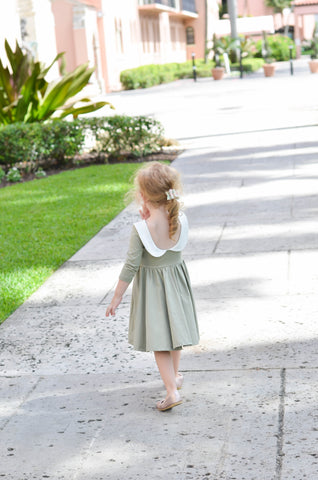 young blonde child walking in an art deco area in an adorable light green dress