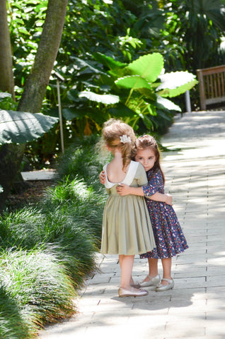 two toddlers hugging in a tropical setting wearing cute twirling dresses
