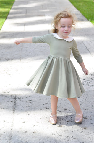 happy young blonde child spinning around on a path in a cute green dress