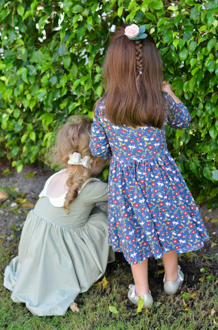 two 3 year old girls peeking through bushes in cute dresses
