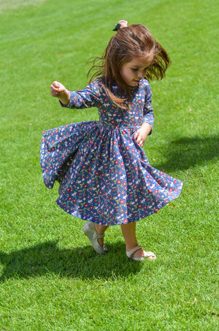 cute toddler girl playing on a field of grass in a vintage floral twirl dress and felt flower bow