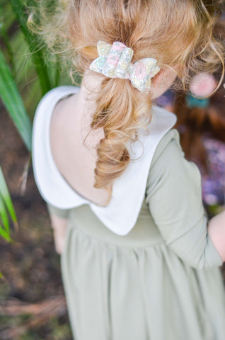 Close up of back of a green twirly dress with peter pan collar