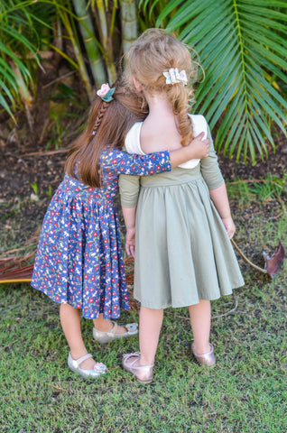 little girls hugging in front of greenery wearing cute twirly dresses
