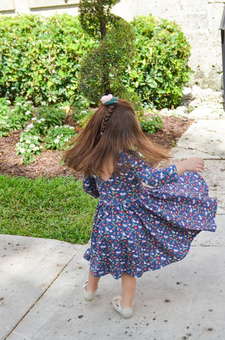 young brunette child twirling around in front of topiaries in a vintage floral dress
