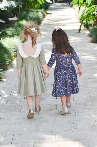 two toddler friends walking down a path holding hands