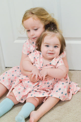 baby and toddler in matching dresses smiling