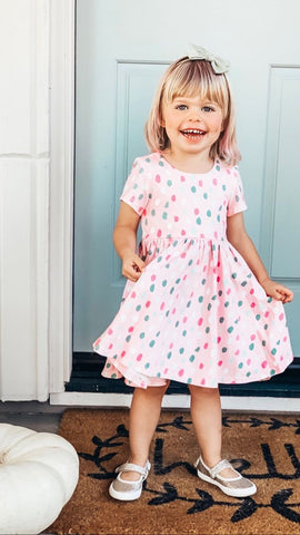 young girl in front of blue door with polka dot twirl dress