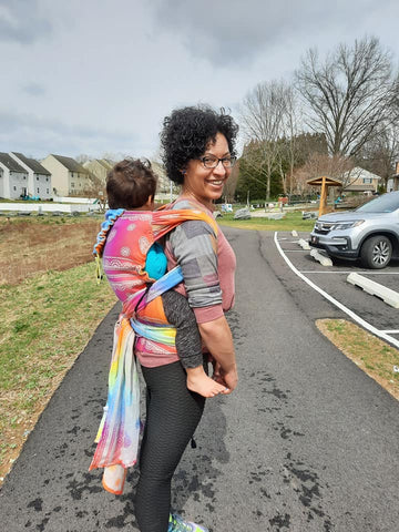 Mom smiling with toddler on her back in Rainbow Lace Silver toddler Lenny Hybrid tester