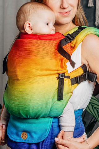 Model holds baby in Lenny Upgrade soft structured baby carrier (SSC, baby backpack), in print Rainbow Baby. The print features large horizontal gradient rainbow stripes