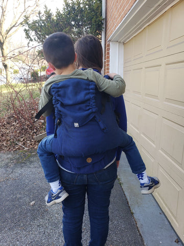 A white brunette woman carries a white brunette child on her back in a herringbone blue Cobalt Preschooler carrier by Lenny Lamb.