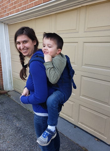 A side view of a white brunette woman carrying a white brunette child in a herringbone blue Cobalt Preschooler carrier by Lenny Lamb, back carry, side view