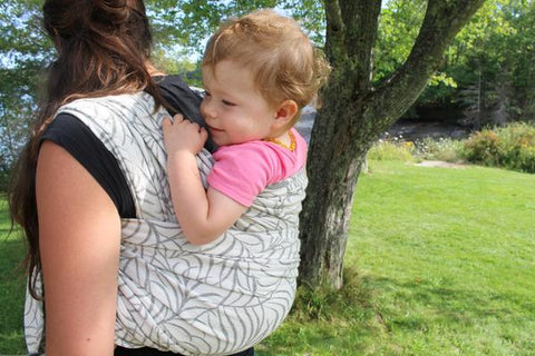 Model wears child on her back outdoors in a grey and white long woven baby wrap by Bijou Wear