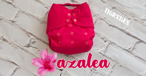 Thirsties limited edition diaper Azalea shown in a duo wrap with matching trim and snaps. A bright pink diaper on gray wooden background. Text: Thirsties Azalea