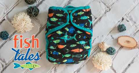 Fish Tales diaper by Thirsties displayed on a white brick background with sea shells and the words Fish Tales. The diaper features brightly colored fish in orange, blue, and green on a black background with teal trim
