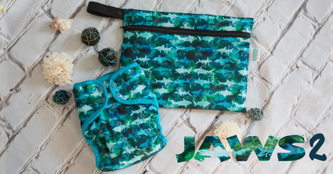 Jaws 2 print diaper and mini wet bag by Thirsties. The print has sharks in blues and greens swimming through watercolor blues and greens with a blue-green trim. The mini wet bag has the same trim with black zipper and black hanging handle