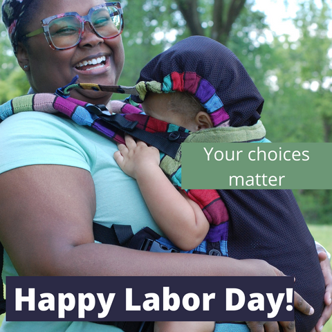 """Text reads, """"Happy Labor Day! Your choices matter."""" Photo is of a black mother wearing her daughter in a Carousel of Colors Lenny Upgrade with Mesh panel. Mom is smiling as her daughter pretends to sleep with the hood up"""