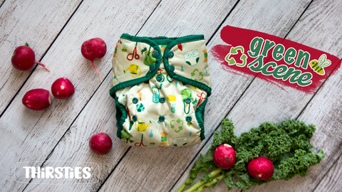 "Thirsties Limited Edition diaper ""green scene"" shown in a pocket diaper with green trim on a wooden board staged with radishes and greens. The diaper is a cream background with images of various ""green"" things like cloth diapers, bikes, sewing scissors, gardening shears, and more"