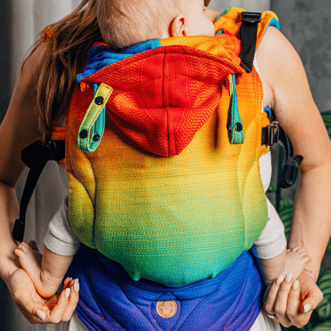 Model holds baby in Lenny Lamb fixed panel soft structured carrier LennyGo in print Rainbow Baby. The print features large horizontal gradient stripes in a rainbow pattern