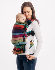 Brunette model is wearing a baby in a Lenny Lamb soft structured baby carrier (SSC or baby backpack) in print Carousel of Colors. This cotton baby carrier has thick horizontal stripes in shades of green, turquoise, red, purple, blue, magenta, and pink with thin black stripes in-between the colors.