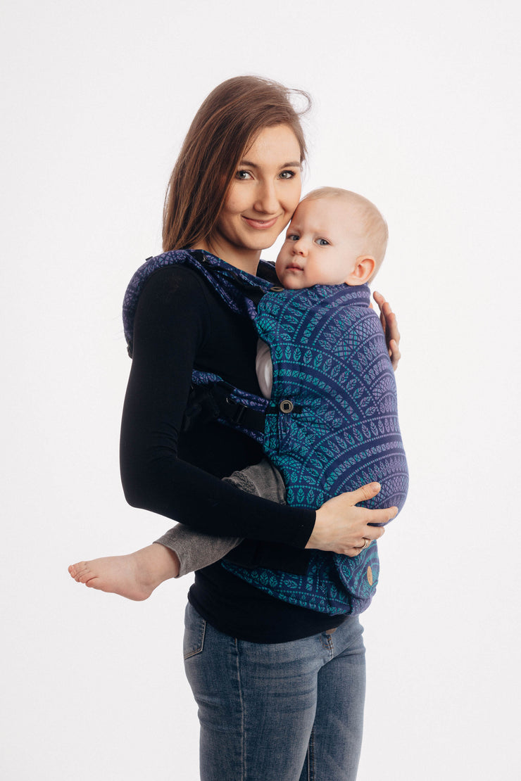 Model wearing a toddler in Lenny Lamb adjustable soft structured baby carrier Lenny Upgrade in print Peacock's Tail Provance