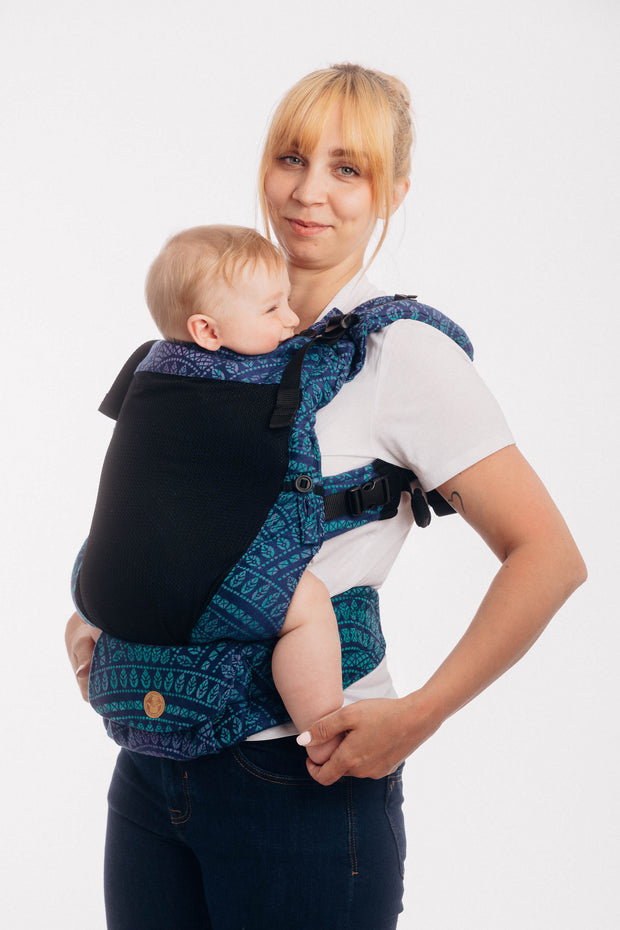 Model wearing a toddler in Lenny Lamb adjustable soft structured baby carrier Lenny Upgrade in print Peacock's Tail Provance with a black mesh front panel
