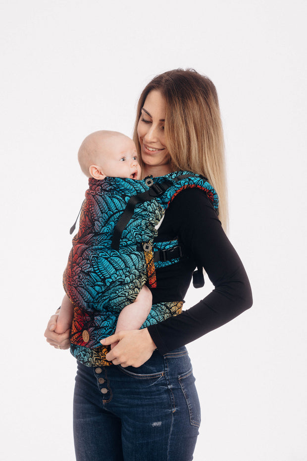 Model wearing a baby in a Lenny Lamb Lenny Upgrade babywearing soft structured carrier (SSC) in print Wild Soul Daedalus