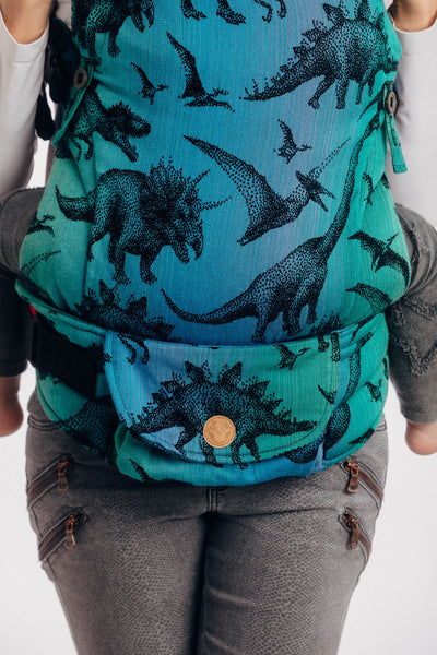 Model wearing a toddler in Lenny Lamb's Lenny Upgrade soft structured baby carrier (SSC) in print Jurassic Park