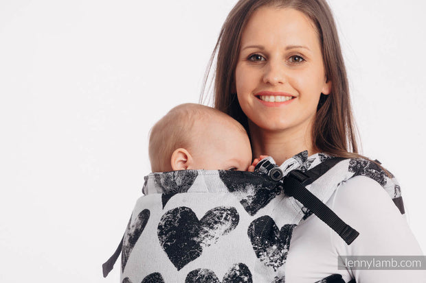 A woman wearing a baby in Lenny Lamb brand fully adjustable soft structured baby carrier (SSC) the Lenny Upgrade. This print is Lovka Classic, a white background with large black hearts with a faux faded look