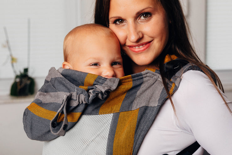 Model wears baby in LennyGo Mesh soft structure ergonomic baby carrier by Lenny Lamb in print Smoky Honey.