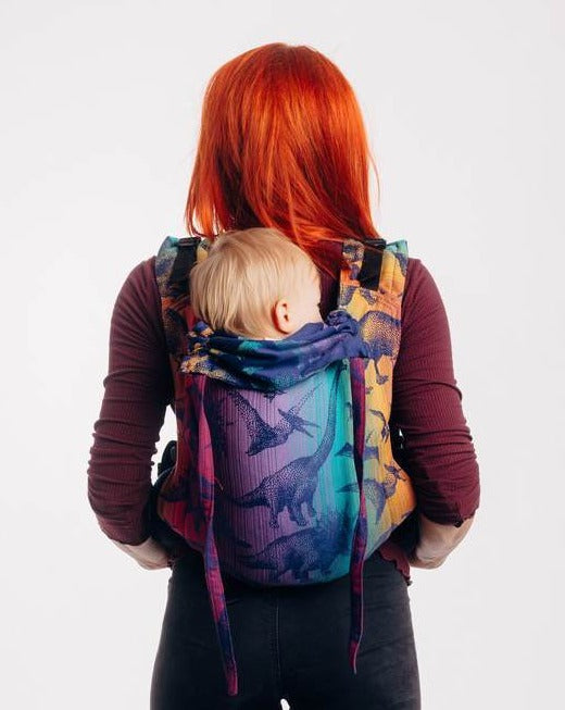 Red haired model is wearing a baby on her back in a Lenny Lamb buckle onbuhimo baby carrier in print Jurassic Park - New Era. The cotton baby carrier has realistic looking dinosaurs in a dark purple weft with background color gradient from gold to teal to purple to magenta