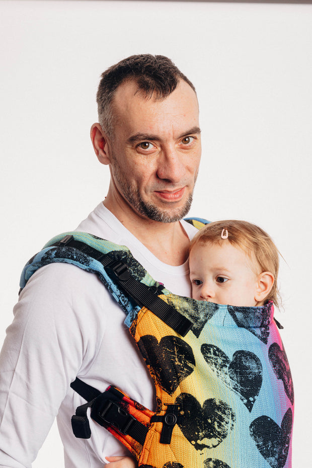 Model wearing a baby in Lenny Lamb's Lenny Upgrade adjustable soft structured baby carrier (SSC) in print Lovka Rainbow Dark