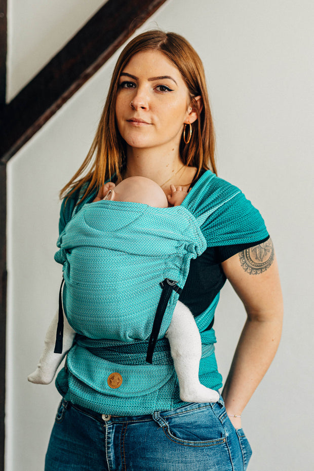 Model wearing demo doll in Lenny Lamb Lenny Hybrid babywearing baby carrier in print Little Herringbone Ombre Teal