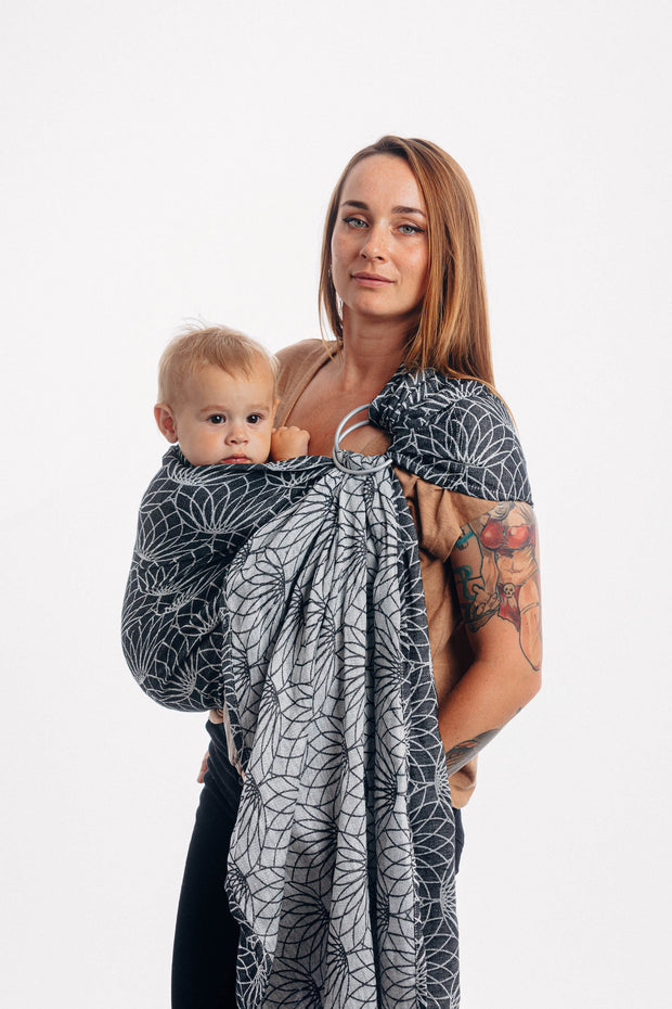 Model wearing baby in Lenny Lamb brand ring sling in Jacquard weave linen, print Lotus - Black. Side view neutral pose