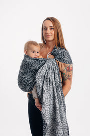 Model wearing baby in Lenny Lamb brand ring sling in Jacquard weave linen, print Lotus - Black. Side view baby hand in mouth.