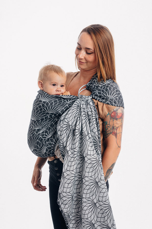 Model wearing baby in Lenny Lamb brand ring sling in Jacquard weave linen, print Lotus - Black. Looking down at baby
