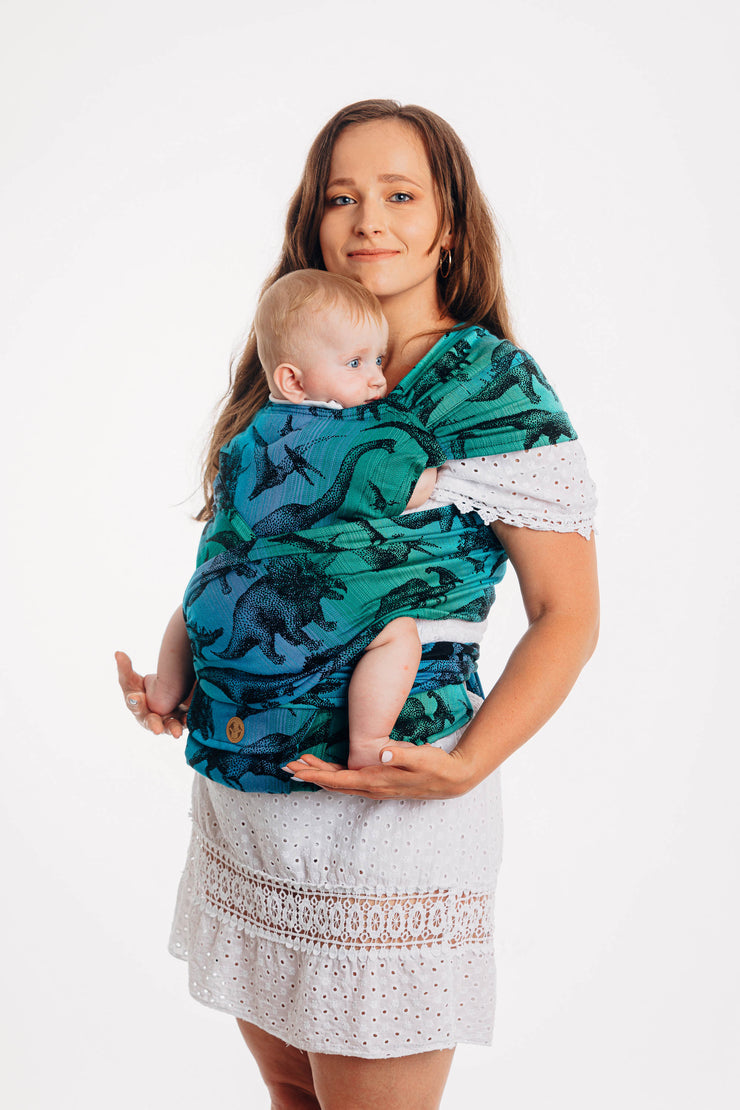Lenny Lamb brand half buckle meh dai baby carrier the Lenny Hybrid in print Jurassic Park. Model is looking at the camera. Full front view.