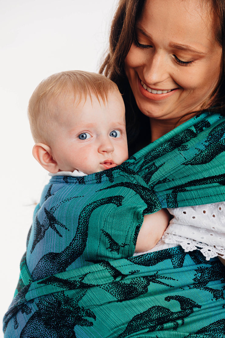 Lenny Lamb brand half buckle meh dai baby carrier the Lenny Hybrid in print Jurassic Park. Model is looking down at baby being worn on her front and smiling