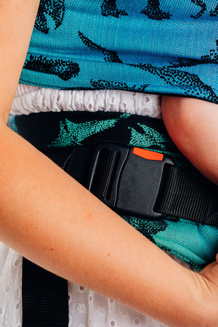 Lenny Lamb brand half buckle meh dai baby carrier the Lenny Hybrid in print Jurassic Park. Close up of wrap strap along the side and buckle on waist