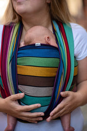 Lenny Lamb Long Woven Wrap - Carousel of Colors - newborn in front wrap cross carry.  Wrap has horizontal stripes in rainbow colors with thin black stripes in-between the colors