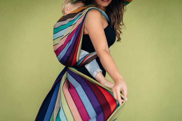 Lenny Lamb Long Woven Wrap - Carousel of Colors - toddler back carry, side view. Wrap has horizontal stripes in rainbow colors with thin black stripes in-between the colors