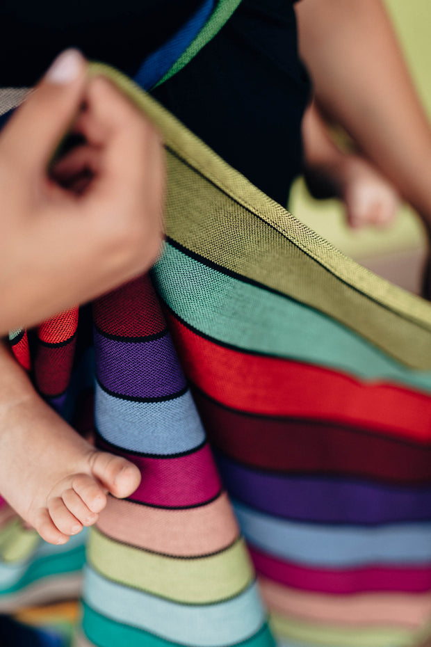 Lenny Lamb Long Woven Wrap - Carousel of Colors - toddler toes, fabric fanned out. Wrap has horizontal stripes in rainbow colors with thin black stripes in-between the colors