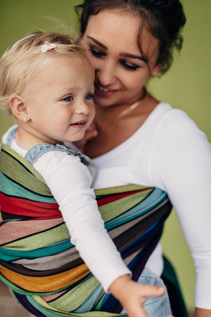 Lenny Lamb Long Woven Wrap - Carousel of Colors - toddler in torso carry front. Wrap has horizontal stripes in rainbow colors with thin black stripes in-between the colors