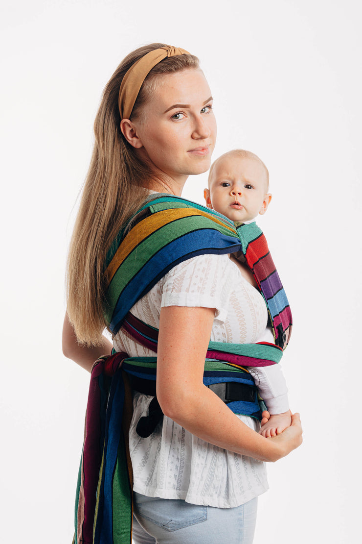 Model wearing baby in Lenny Lamb brand Lenny Hybrid half buckle meh dai carrier in print Carousel of Colors. A view of the back of the carrier showing crossed straps and tails. Baby and model are looking to camera. Hood is removed for photo