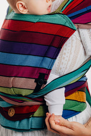 Model wearing baby in Lenny Lamb brand Lenny Hybrid half buckle meh dai carrier in print Carousel of Colors. A close up view showing the panel, pocket, height adjuster, and side. Hood is removed for photo