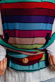 Model wearing baby in Lenny Lamb brand Lenny Hybrid half buckle meh dai carrier in print Carousel of Colors. A close up view showing the panel, pocket, height adjusters, and tie off under baby's bum.