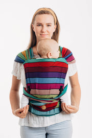 Model wearing baby in Lenny Lamb brand Lenny Hybrid half buckle meh dai carrier in print Carousel of Colors. A full front view showing the panel, pocket, height adjusters, and tie off under baby's bum. Hood is removed for photo